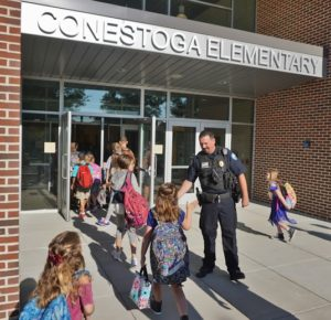 Picture of police officer greeting students on first day of school