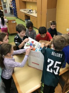 Students opening and unpacking a box of books for the library