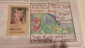 Picture of student with a winning advertising drawing that was published in the newspaper for NIE